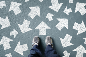 Metaphor - two feet standing in front of lots of arrows - which way is the right way